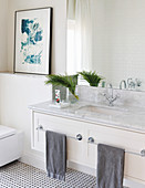 Washstand with marble top and two towel rails in bright bathroom