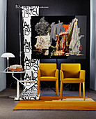 Yellow chairs and side table in front of photographic artwork and roll of wallpaper