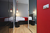 Wardrobes and mirrors in narrow corridor leading to bedroom