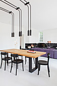 Pairs of pendant lamps above dining table in front of sofa