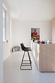 Black bar stools at pale wooden island counter in bright kitchen