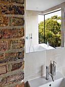 Modern bay window reflected in mirror in bathroom with brick wall