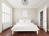 Schlafzimmer ganz in Weiß mit Holzboden
