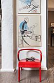 Roter Stuhl vor der Wand mit Gemälden