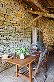Set table in converted barn with stone wall