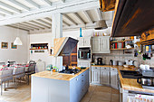 Open-plan country-house kitchen and dining area with wood-beamed ceiling