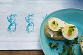 Baguette mit Ei auf österlicher Tischdecke dekoriert mit Hasenmotiven