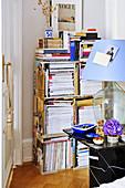 Nachttischlampe mit Ballonflasche als Lampenfuß und offenes Bücherregal im Schlafzimmer