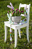Bunch of tulips and hand-made fabric bunnies in basket and garland of eggs on chair in garden