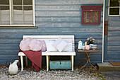 Verschiedene Kissen mit selbst genähten Kissenbezügen auf Bank vor Holzhaus