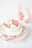 Teacup filled with ranunculus and roses in front of Easter bunnies