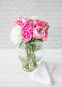 Peonies in glass vase