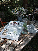 A homemade scrabble coaster and a wooden tray with glasses on a garden table