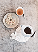 Homemade coasters, a teapot, a teacup and cinnamon buns