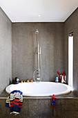 Badezimmer mit ovaler Badewanne und Spritztieren