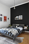 Graues Doppelbett auf Tierfellteppich im Schlafzimmer mit schwarz-weissen Wänden