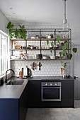Steel and wood shelves on white-tiled wall in kitchen