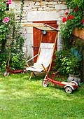 Liegestuhl und altes Spielzeug auf dem Rasen vor einem Steinhaus