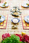 Gedeckter Tisch mit Mosaikplatte in Rot und Gelb