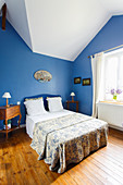 French bedroom with sloping ceiling and blue walls