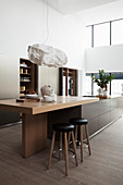 Island counter with breakfast bar extension in open-plan kitchen