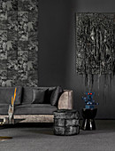 Back velvet sofa and stool in front of black wall