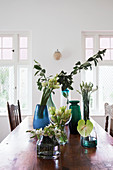 Glass vases of flowers and leafy branches on rustic dining table
