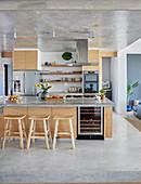 Offene Küche mit Kochinsel, Barhockern und hellen Holzfronten und auf Betonpodest