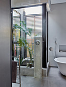 Glass door and grey-painted walls in ensuite bathroom