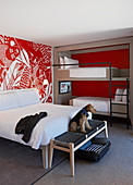 Double bed and bunk beds in modern hotel room with red and white wallpaper; dog on bedroom bench