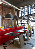 Red bench, grey tables and chairs in restaurant