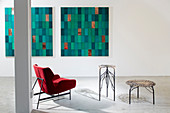 Designer armchair and artistic side tables in front of two artworks