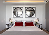 Two round mirrors in square frames above bed with red pillows