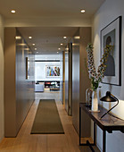 Modern hallway with panelled walls and view into living room