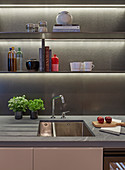 Open kitchen shelves with indirect lighting above sink
