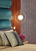 Pendant lamps in golden rings next to bed