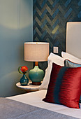 Bedside lamp next to bed with red scatter cushion against blue patterned wallpaper