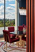 Rote Samtstühle mit goldenem Gestell im Esszimmer mit Panorama