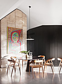 Round table with chairs under pendant lamp, artwork on the wall