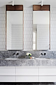 Bright bathroom with double vanity and mirror cabinets and white wall tiles