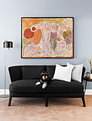 Black sofa with pillows and dog next to standard lamp, modern art on the wall