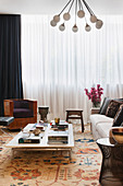 Low coffee table, upholstered sofa with cushions and cherry wood armchair in the living room with floor-length curtains