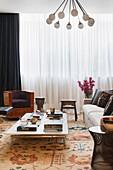 Niedriger Couchtisch, Polstersofa mit Kissen und Sessel aus Kirschholz im Wohnzimmer mit bodenlanger Gardine
