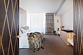 Blick durch geöffnete Flügeltür auf Doppelbett mit Felldecke im eleganten Schlafzimmer