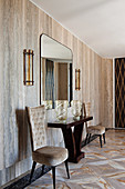 Console table with glass vases, chairs and wall mirror in elegant hallway with travertine wall covering