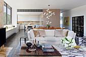 Couchtisch aus Ebenholz und Messing, daneben Blumenstrauß auf Marmor-Couchtisch, im Hintergrund helles Sofa in offenem Wohnraum