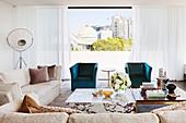 Marmor-Couchtisch neben Couchtisch aus Ebenholz und Messing, elegante Sofagarnitur und türkisfarbene Sessel vor Fenster in Penthauswohnung