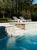 Natural stone terrace with pool and sun beds
