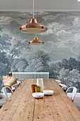 Long wooden table and chairs in front of mural wallpaper