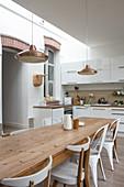 Langer Massivholztisch mit Stühlen in offener, weißer Küche